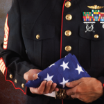 Uniformed soldier holding a flag