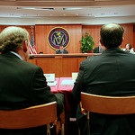 Two men sit in a hearing at the FCC