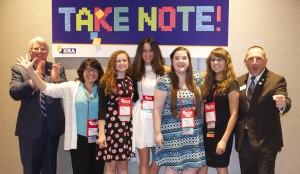 Court reporting students and the NCRA president and CEO stand in front of the Take Note campaign sign