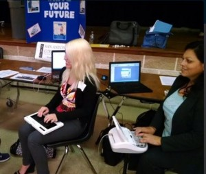 A court reporting student and a court reporter writing on their steno machines at a career fair