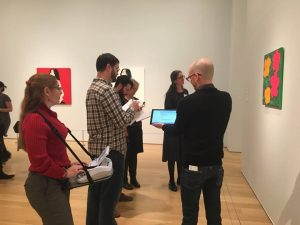 Cathy Rajcan, on left, writes on her steno machine, which is strapped to her with a harness. At right, a tour guide talks about a piece of art for a museum guest.