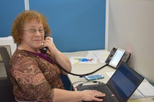 Kathy Cortopassi on the phone sitting at a desk