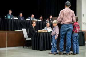 At a long skirted table on an auditorium stage sit five people in professional attire; at a skirted table on the floor sit two court reporters; in front, with their backs to the camera, are a father and his two young sons, all three dressed in jeans, plaid shirts, boots, and ball caps