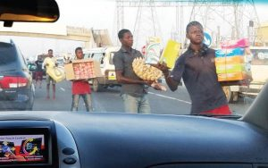 View is through the windshield of a car as if sitting in the passenger seat. A line of street vendors walk along the car holding various wares for sale. They are looking ahead.