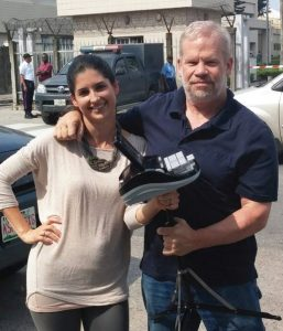 A young woman and an older man are facing the camera with their arms congenially around each other's shoulders as if friends. The woman is holding a steno machine on a tripod.