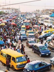A street scene in Lagos: A narrow paved street with a line of cars (sometimes single file, sometimes double file), cars parked or waiting to move on either side of the street, pedestrians crowded mostly on the left side. Near the background, a cluster of colorful umbrellas. In the back, white nondescript buildings. At the top in the foreground and background are electrical wires.
