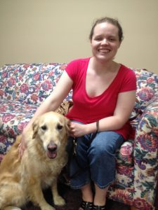 A smiling young adult woman, dressed cassually, sits on a floral couch with a golden retriever at her side.