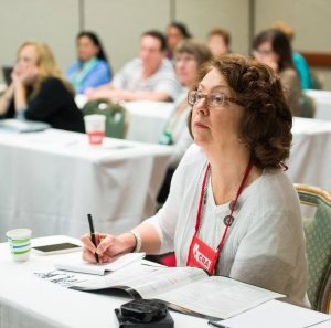 A middle-aged white woman listens attentively during a workshop while taking notes.