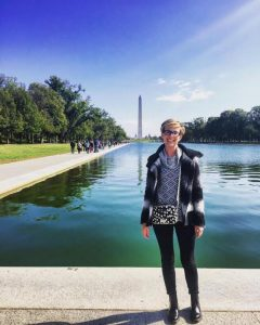 A young blond woman standing in front of the reflection pool with the Washington Monument in the background