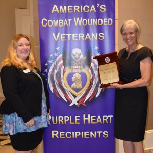 "Two women, one holding a plaque in the shape of a scroll, stand in front of a banner reading ""America's Combat Wounded Veterans -- Purple Heart Recipients."" The wording is wrapped around an image of the Purple Heart medal in front of a bald eagle whose wings turn into the American flag."