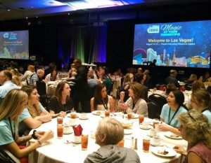 A large luncheon in a hotel ballroom with people seated at round tables; in the background is the logo for the 2017 NCRA Convention & Expo