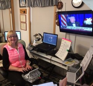 A woman sits in front of a steno machine, set up to work from home. On her desk is her laptop and paper notes propped up for easy viewing. On the wall is a television screen with a news show.