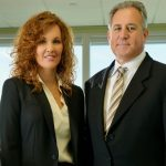 Photo of NCRF Major Gifts donors: A man and a woman in professional attire stand side by side in an office