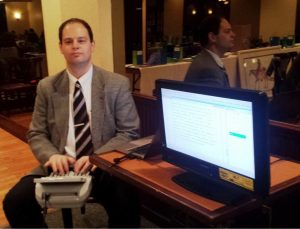 Man in a suit sitting at a steno machine next to a screen