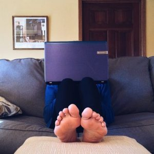 Front view of a person sitting barefoot on a couch with their laptop on their knees, blocking their face